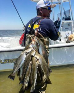 Man presenting several Speckled Trout on his back caught at the Galveston Bay Fishing Rodeo