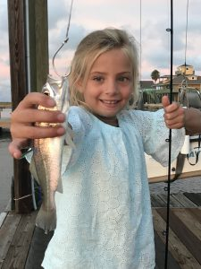 Girl holding fish on hook in Galveston Texas