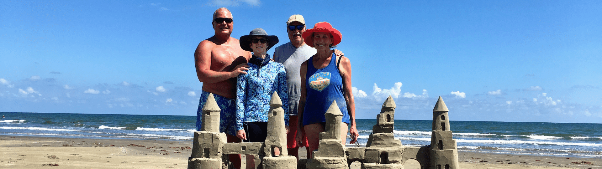 Family standing in front of sand castle in Galveston tx