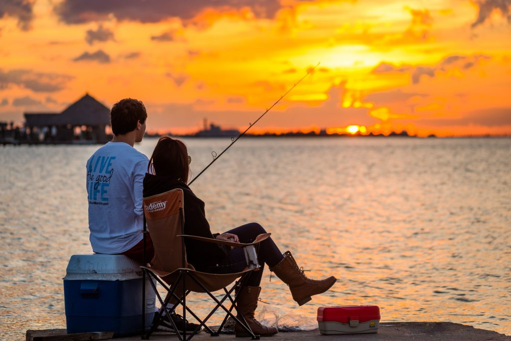 Two people fishing at sunset, overlooking the bay