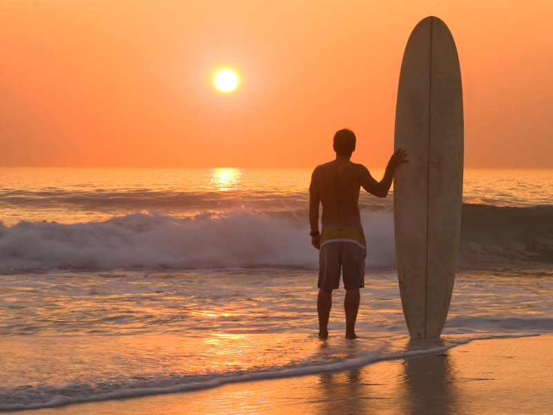 Man with surf board at sunrise