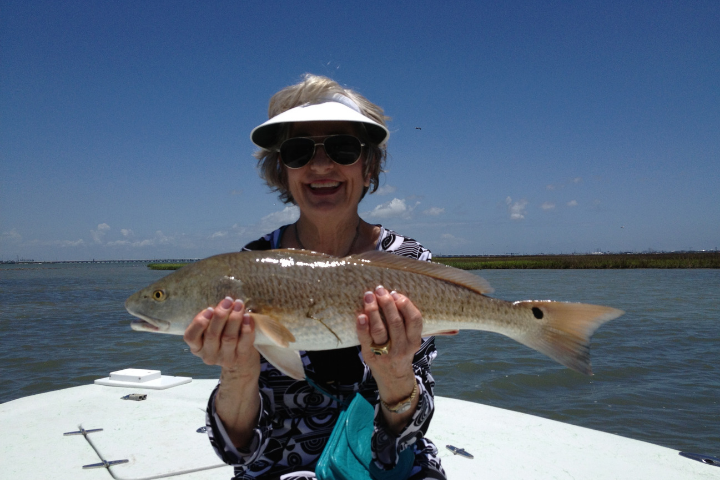 Woman holding a large fish and smiling.
