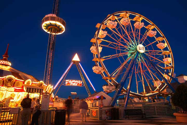 Galveston Island pier at sunset with fair attractions light up.