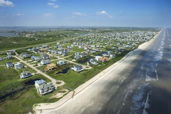 Aerial image of Galveston, Texas coastline featuring beach homes, sand, and the ocean.
